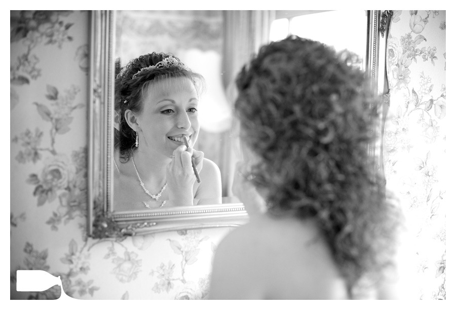 bride putting on makeup on wedding morning